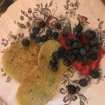 Vegane Pfannkuchen - auf dem Teller mit Blaubeeren und Erdbeeren angerichtet